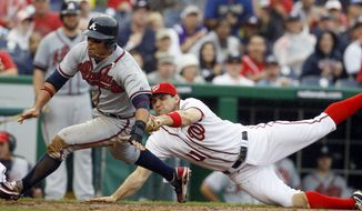 Atlanta Braves' Martin Prado, left, is run down on his way to the plate by Washington Nationals third baseman Ryan Zimmerman (11) during the eighth inning of the first baseball game of a doubleheader, Saturday, July 21, 2012, in Washington. The Braves won 4-0. (AP Photo/Carolyn Kaster)
