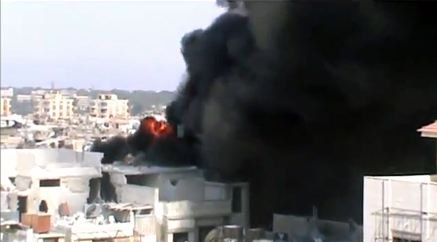 This image made from amateur video released by Shaam News Network and accessed by the Associated Press on purports to show the spread of fires as a result of the shelling of Homs, Syria, by government forces on July 21, 2012. (Associated Press/Shaam News Network via AP video)