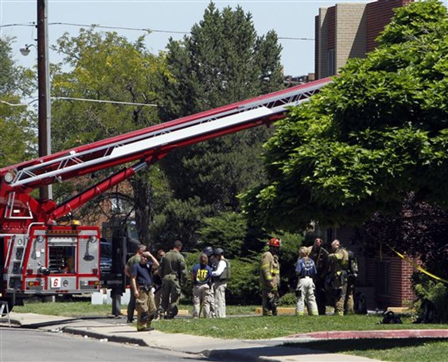 """Firefighters and police gather after an explosion could be heard outside the apartment of James Holmes in Aurora, Colo., Saturday, July 21, 2012. Federal authorities detonated one small explosive and disarmed another inside Holmes' apartment, but several other explosive devices remained, said Aurora police Sgt. Cassidee Carlson. Twelve people were killed and dozens were injured in a shooting attack early Friday at a packed movie theater during a showing of the Batman movie, """"The Dark Knight Rises."""" Police have identified Holmes, 24, as the suspected shooter. (AP Photo/Ed Andrieski)"""