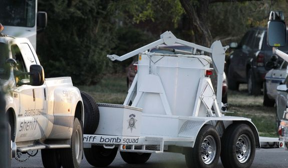 A bomb disposal vehicle arrives July 21, 2012, near the Aurora , Colo., apartment of  James Holmes, the alleged gunman in an assault at a movie theater that left 12 dead and more than three dozen people injured. (Associated Press)