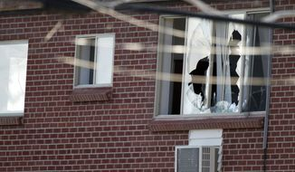 "Windows are broken July 20, 2012, at the Aurora, Colo., apartment of James Holmes, 24, the alleged gunman in an assault at a theater during a midnight premiere of ""The Dark Knight."" Twelve died and more than three dozen people were shot in the assault. (Associated Press)"