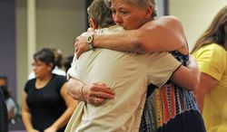 Joyce Young hugs her 13-year-old grandson, Justin Haynes, at the Restoration Christian Fellowship in Aurora on Sunday. Shooting suspect James Holmes, whose apartment also was booby-trapped with explosives, is slated to appear in court for the first time Monday. (Associated Press)
