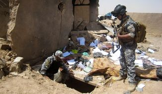 ** FILE ** In this Tuesday, April 20, 2010, file photo, Iraqi policemen search the site of a joint U.S-Iraqi raid that killed Abu Omar al-Baghdadi and Abu Ayyub al-Masri, two top-ranking al Qaeda figures, about six miles (10 kilometers) southwest of Tikrit. The first online statement from the new leader of al Qaeda's affiliate in Iraq claims that the militant network is returning to the old strongholds from which it was driven by U.S. forces and their Sunni allies prior to the American withdrawal at the end of last year, and that it is preparing operations to free prisoners and assassinate court officials. (AP Photo, File)