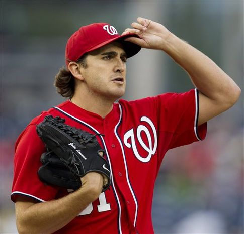 Washington Nationals starting pitcher John Lannan pauses in the first inning during the second baseball game of a doubleheader against the Atlanta Braves, Saturday, July 21, 2012. Lannan gave up two runs in the first inning but none in the next six in a game the Nationals went on to win 5-2. (AP Photo/Carolyn Kaster)