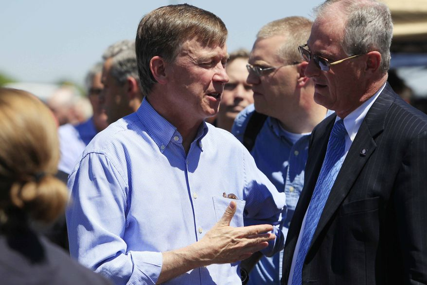 ** FILE ** Colorado Gov. John Hickenlooper, left, confers with Steve Hogan, mayor of Aurora, Colo., before a news conference at the Century 16 theater east of the Aurora Mall in Aurora, Colo., on Friday, July 20, 2012. (AP Photo/David Zalubowski)