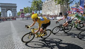 Bradley Wiggins of Britain, wearing the overall leader's yellow jersey, is followed by teammate Mark Cavendish of Britain and Peter Sagan of Slovakia, wearing the best sprinter's green jersey, as they pass the Arc de Triomphe during the 20th stage of the the Tour de France cycling race over 120 kilometers (74.6 miles) with start in Rambouillet and finish in Paris, France, Sunday, July 22, 2012. (AP Photo/Christophe Ena)