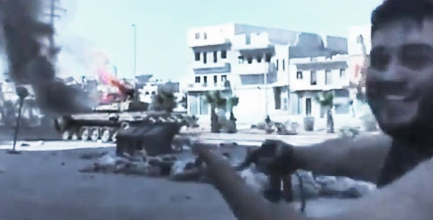 In this image made from amateur video, a Free Syrian Army soldier Monday points toward a military tank set on fire during clashes with government troops in Aleppo. The Syrian regime acknowledged for the first time Monday that it possessed stockpiles of chemical and biological weapons. (Ugarit News via Associated Press)
