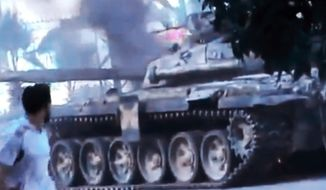 In this image made from amateur video released by the Ugarit News and accessed Monday, July 23, 2012, a Free Syrian Army soldier looks at a Syrian military that caught on fire during clashes with Syrian government troops in Aleppo, Syria. The Syrian regime acknowledged for the first time Monday that it possessed stockpiles of chemical and biological weapons and said it will only use them in case of a foreign attack and never internally against its own citizens. The Associated Press cannot independently verify the content, date, location or authenticity of this material. (AP Photo/Ugarit News via AP video)