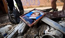A portrait of Russian President Vladimir Putin rests on a pile of debris at a flooded house in Krimsk, about 750 miles south of Moscow. Flooding killed more than 170 in southern Russia on July 6 and 7. The president is taking heat for a fumbled early warning. (Associated Press)