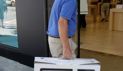 **FILE** An Apple customer returns a 21.5-inch iMac computer to an Apple Store in Palo Alto, Calif. (Associated Press)