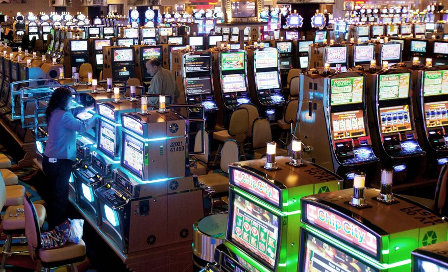 **FILE** Workers put the finishing touches on slot machines at Hollywood Casino, in Perryville, Md. (Associated Press)