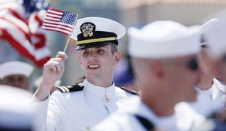 A sailor waves a flag during a gay pride parade Saturday in San Diego. A GOP senator from Oklahoma is calling on the defense secretary to explain why an exception was made to rules barring the wearing of uniforms at political activities. (Associated Press)