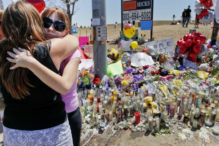 """Stacy Fleming, 23, second from left, hugs her friend Pam Frakes Monday, July 23, 2012, at a make-shift memorial that the public created across the street from the Century Theater where a mass shooting occurred last Friday killing 12 and injuring dozens of others in Aurora, Colo. Fleming and her boyfriend decided to go to another theater to watch """"The Dark Knight Rises"""" at the last minute. (AP Photo/Barry Gutierrez)"""