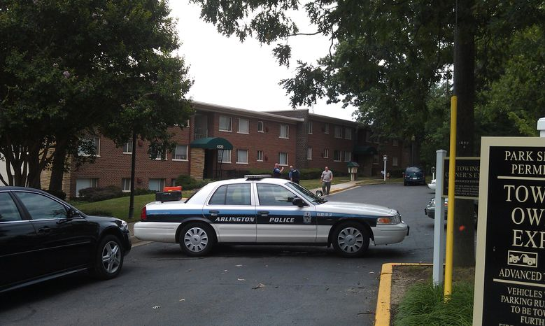 Police officers restrict access to a Shirlington apartment complex where a man and woman were found dead in an apparent murder-suic
