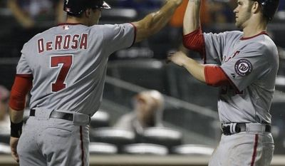 Washington Nationals Mark DeRosa (7) and Washington Nationals Bryce Harper (34) celebrate after they scored on Ryan Zimmerman's 10th-inning, three-run double in their 8-2 victory over the New York Mets in a baseball game at Citi Field in New York, Monday, July 23, 2012. (AP Photo/Kathy Willens)