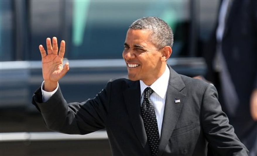 President Obama waves upon his arrival, Tuesday, July 24, 2012, at the 142nd Fighter Wing Oregon Air National Guard Base, in Portland, Ore. Mr. Obama is in Oregon to raise money for his re-election campaign. (AP Photo/Rick Bowmer)