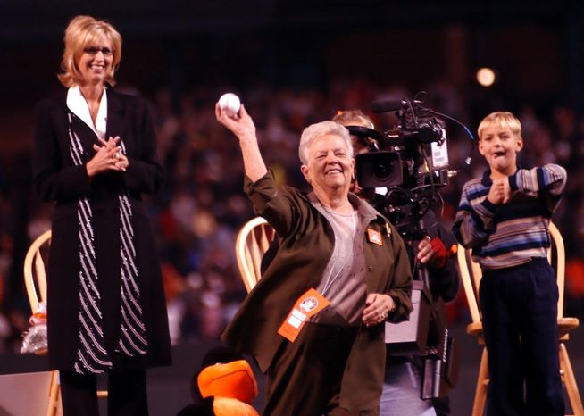 **FILE** Violet Ripken (center), mother of Baltimore Orioles legend Cal Ripken Jr., throws out the first pitch of the Orioles game with the Boston Red Sox on October 6, 2001 at Camden Yards. Looking on are Cal Ripken's wife, Kelly, and their son, Ryan. (The Washington Times)