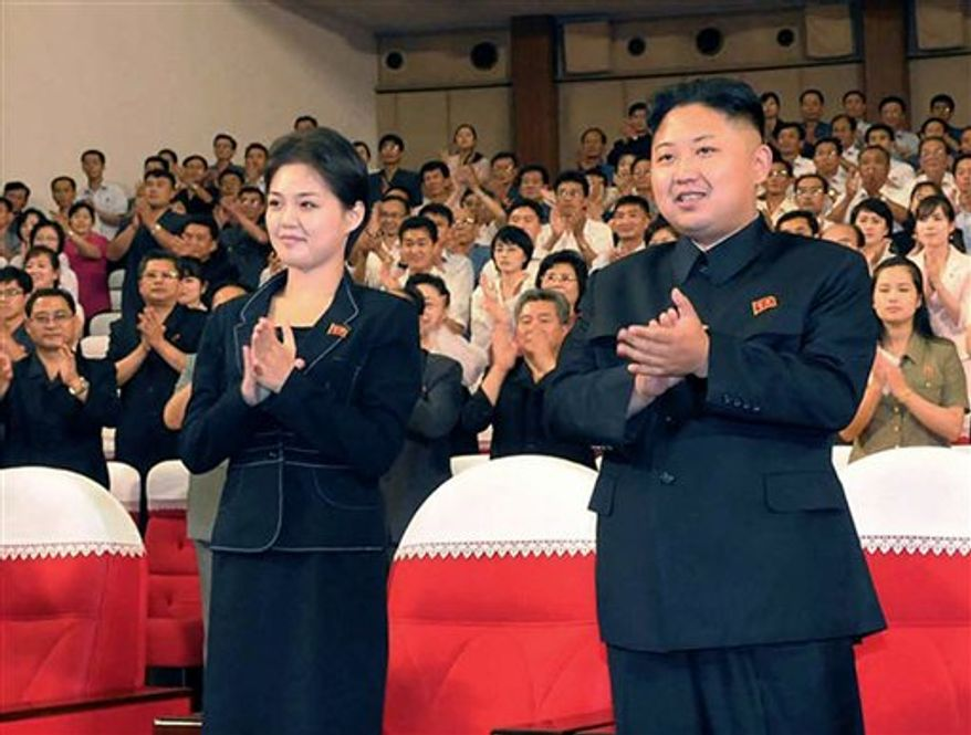 """FILE - This is a file photo made available on Monday July 9, 2012 by the Korean Central News Agency (KCNA) and distributed in Tokyo by the Korea News Service of North Korean leader Kim Jong Un, right, and Ri Sol Ju as they clap with others during a performance by North Korea's new Moranbong band in Pyongyang, North Korea earlier in July. North Korea's new, young leader Kim Jong Un is married, state TV reported Wednesday July 25, 2012 for the first time in a brief and otherwise routine announcement that ends weeks of speculation about a beautiful woman who has accompanied him to recent public events. Kim toured an amusement park with his """"wife, comrade Ri Sol Ju"""" on Tuesday, while a crowd cheered for the leader, the news anchor said without giving any more details about Ri, including how long they had been married. (AP Photo/Korean Central News Agency via Korea News Service, File)"""