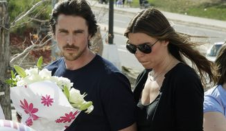 "Actor Christian Bale and his wife Sibi Blazic visit July 24, 2012, a memorial in Aurora, Colo., for the victims of a mass shooting that left 12 people dead. A a gunman opened fire during a late-night showing of the movie ""The Dark Knight Rises,"" which stars Bale as Batman. (Associated Press)"