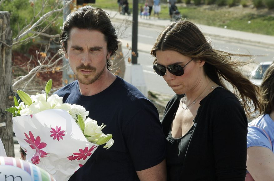 """Actor Christian Bale and his wife Sibi Blazic visit July 24, 2012, a memorial in Aurora, Colo., for the victims of a mass shooting that left 12 people dead. A a gunman opened fire during a late-night showing of the movie """"The Dark Knight Rises,"""" which stars Bale as Batman. (Associated Press)"""
