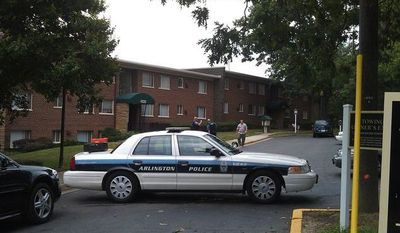 Police officers restrict access to a Shirlington apartment complex where a man and woman were found dead in an apparent murder-suicide (Charity Corkey/The Washington Times)