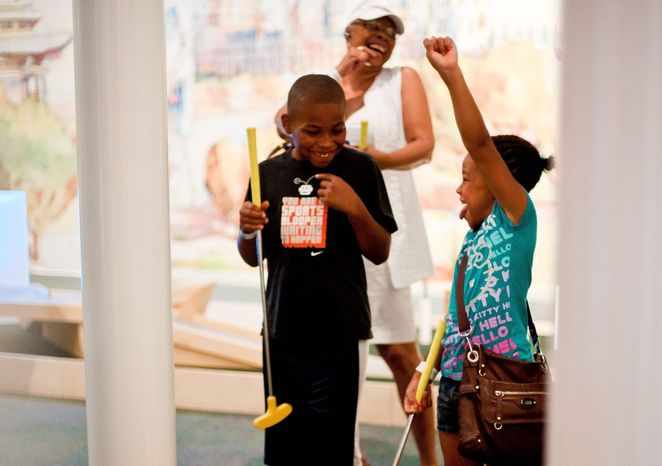 Genay Tolbert, 7, reacts to getting a hole-in-one while playing a round of minigolf with her brother Geo-Di, 10, and grandmother Julia. The exhibit at the National Building Museum has attracted 4,500 visitors since opening on the Fourth of July. It runs through Labor Day. (Ryan M.L. Young/The Washington Times)