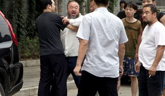 Ai Weiwei, second from left, stopped by a plain clothes policeman while he argues with another policeman, foreground, outside his home in Beijing Wednesday, June 20, 2012. Chinese police on Wednesday barred Ai from attending the first hearing of a lawsuit brought by his company against Beijing tax authorities and blocked reporters from filming at the courthouse, part of an intimidation campaign aimed at silencing the prominent artist and outspoken government critic. (AP Photo/Andy Wong)
