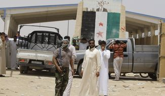 Armed Syrian rebels stand guard July 25, 2012, as refugees flee Syria at the border crossing by the Iraqi town of Qaim, 200 miles (320 kilometers) west of Baghdad. (Associated Press)