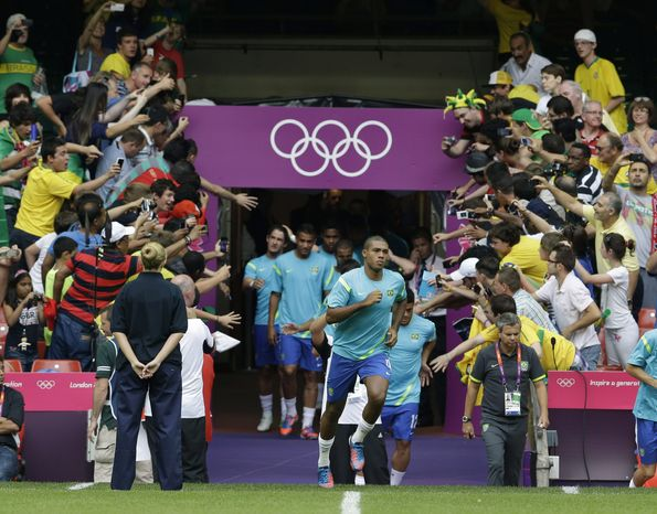 Brazil's Juan Jesus followed by his teammates enters the field of play prior to the start of the men's group C soccer match between Brazil and Egypt, at the Millennium Stadium in Cardiff, Wales, at the 2012 London Summer Olympics, Thursday, July 26, 2012. (AP Photo/Luca Bruno)