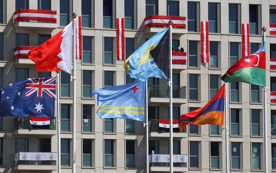 National flags fly in the Olympic Village ahead of the Summer 2012 Olympics on Thursday, July 26, 2012, in London. The opening ceremonies for the 2012 London Olympics will be held Friday, July 27. (AP Photo/Alexander Hassenstein, Pool)
