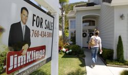 **FILE** A woman walks to an open house in San Diego on June 13, 2012. (Associated Press)