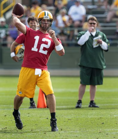 Green Bay Packers quarterbacks coach Ben McAdoo watches quarterback Aaron Rodgers (12) throw the ball during the team's NFL football training camp, Thursday, July. 26, 2012, in Green Bay, Wis. (AP Photo/Mike Roemer)