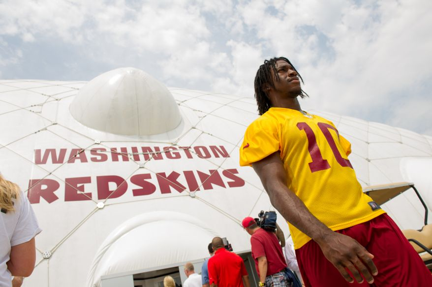 Washington Redskins quarterback Robert Griffin III (10) leaves the indoor training dome as the Washington Redskins finish morning walk-throughs on the first day of training camp at Redskins Park, Ashburn, Va., Thursday, July 26, 2012. (Andrew Harnik/The Washington Times)