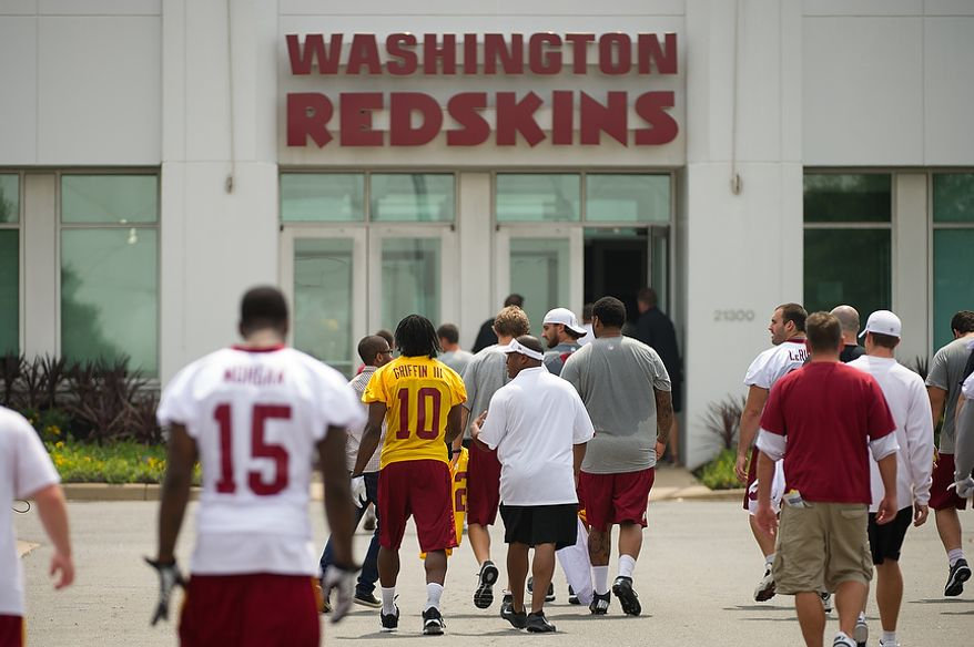 Washington Redskins quarterback Robert Griffin III (10), center, leaves the indoor training dome along with other players and staff as they finish morning walkthroughs on the first day of training camp at Redskins Park, Ashburn, Va., Thursday, July 26, 2012. (Andrew Harnik/The Washington Times)