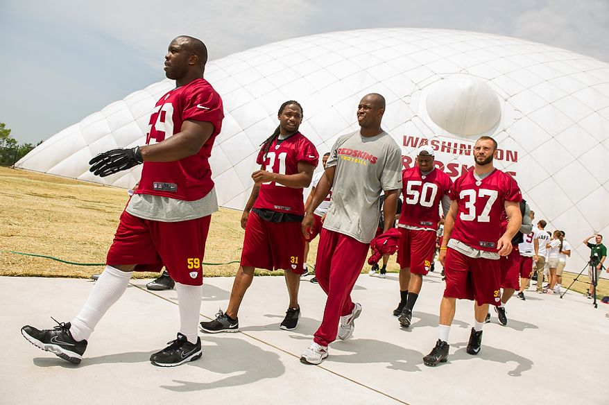 Washington Redskins linebacker London Fletcher (59), left, and other players leave the indoor training dome as the Washington Redskins finish morning walkthroughs on the first day of training camp at Redskins Park, Ashburn, Va., Thursday, July 26, 2012. (Andrew Harnik/The Washington Times)
