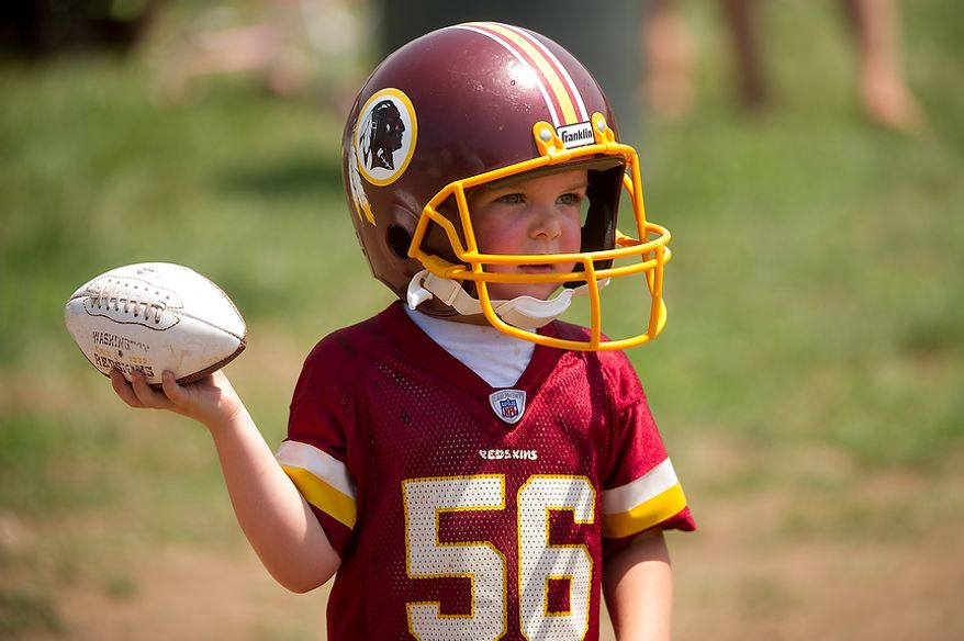 Daxton Williams, 4, of Cumberland, Pa. plays with a football on the first day of training camp at Redskins Park, Ashburn, Va., Thursday, July 26, 2012. (Andrew Harnik/The Washington Times)