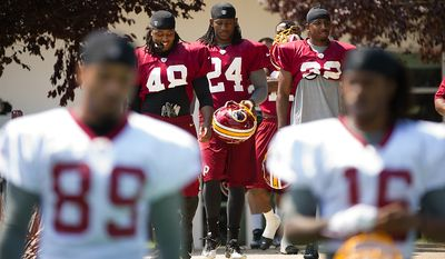 Washington Redskins cornerback Jordan Bernstine (48), left  defensive back DeJon Gomes (24), center, and defensive back Brandyn Thompson (32), right, make their way to the field for afternoon practice on the first day of training camp at Redskins Park, Ashburn, Va., Thursday, July 26, 2012. (Andrew Harnik/The Washington Times)