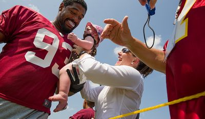 Kate Kohler of Arlington, Va., hold up her 11 month old daughter Monica S. for Washington Redskins defensive end Kentwan Balmer (93) to hug as he makes his way to the field for afternoon practice on the first day of training camp at Redskins Park, Ashburn, Va., Thursday, July 26, 2012. (Andrew Harnik/The Washington Times)