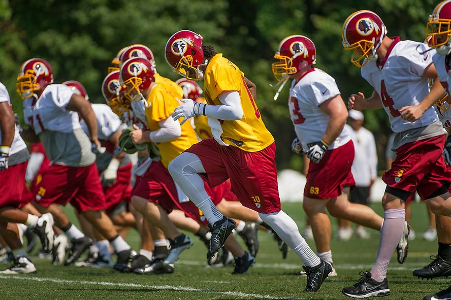 Washington Redskins quarterback Robert Griffin III (10), center, warms up during afternoon practice on the first day of training camp at Redskins Park, Ashburn, Va., Thursday, July 26, 2012. (Andrew Harnik/The Washington Times)