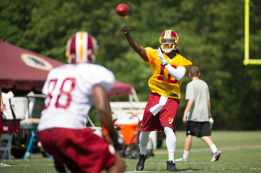 Washington Redskins quarterback Robert Griffin III (10), right, completes a pass during afternoon practice on the first day of training camp at Redskins Park, Ashburn, Va., Thursday, July 26, 2012. (Andrew Harnik/The Washington Times)
