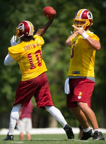 Washington Redskins quarterback Robert Griffin III (10), left, and quarterback Jonathan Crompton (3), right, complete passes during afternoon practice on the first day of training camp at Redskins Park, Ashburn, Va., Thursday, July 26, 2012. (Andrew Harnik/The Washington Times)