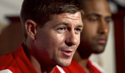 Liverpool FC captain Steven Gerrard, left, faces reporters as teammate Glen Johnson, right, looks on during a news conference held before a training session at Fenway Park baseball stadium, in Boston, Tuesday, July 24, 2012. Liverpool are to play Roma in a friendly soccer game at Fenway Park on Wednesday. (AP Photo/Steven Senne)