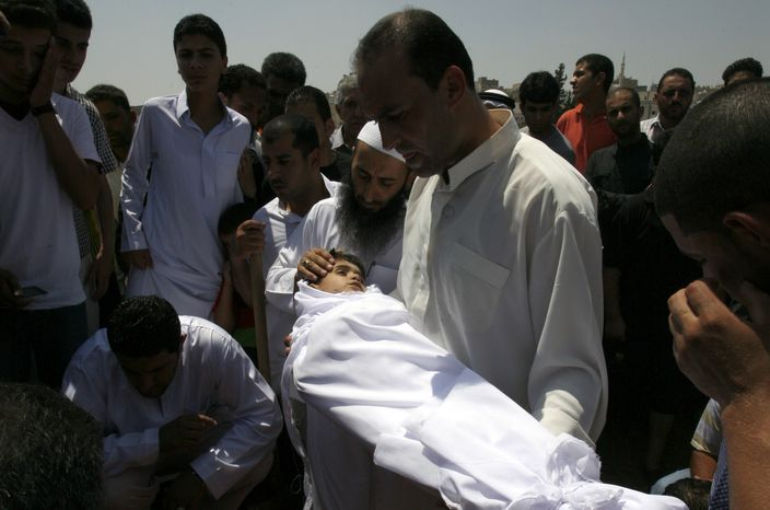 A relative holds the body of a 6-year-old Syrian boy Bilal El-Lababidi during his funeral July 27, 2012, in Ramtha, Jordan. The boy was shot dead by Syrian army as his parents and a dozen other refugees tried to cross a border to seek refuge in Jordan, his mother said. (Associated Press)