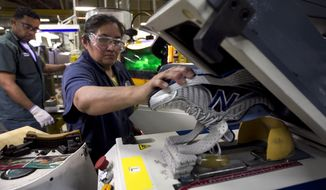 **FILE** Worker Maria Contrero removes an elite running shoe from a sole press May 1, 2012, during the assembly process at the New Balance Athletic Shoe, Inc. factory in Boston. (Associated Press)