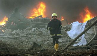 **FILE** A firefighter runs through the blast site after a garbage truck exploded near a hotel used by western contractors in central Baghdad on March 9, 2005. (Associated Press)