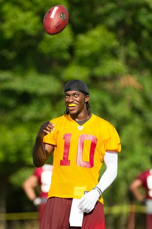 Washington Redskins quarterback Robert Griffin III (10), center, laughs with a teammate following afternoon practice on the first day of training camp at Redskins Park, Ashburn, Va., Thursday, July 26, 2012. (Andrew Harnik/The Washington Times)