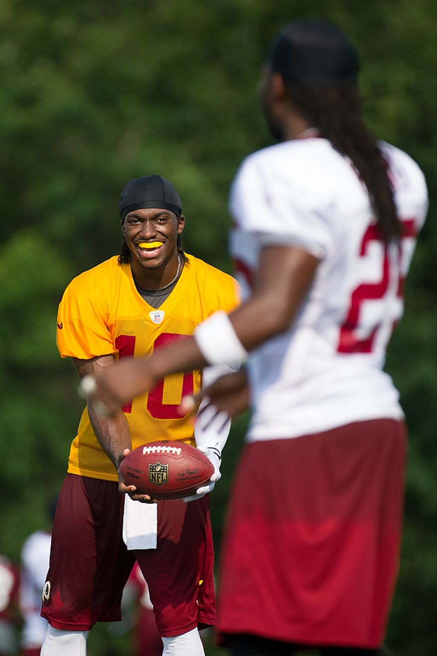 Washington Redskins quarterback Robert Griffin III (10), left, throws with running back Tim Hightower (25), right, following afternoon practice on the first day of training camp at Redskins Park, Ashburn, Va., Thursday, July 26, 2012. (Andrew Harnik/The Washington Times)
