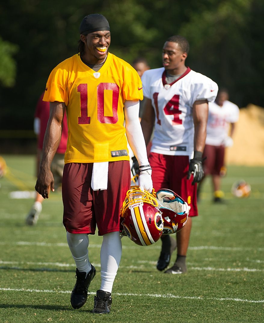 Washington Redskins quarterback Robert Griffin III (10), left, smiles as fans call for him following afternoon practice on the first day of training camp at Redskins Park, Ashburn, Va., Thursday, July 26, 2012. (Andrew Harnik/The Washington Times)