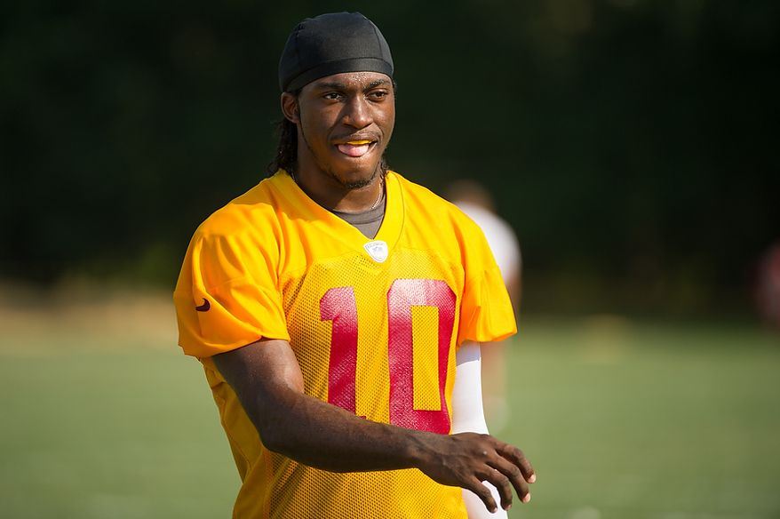 Washington Redskins quarterback Robert Griffin III (10) leave the field following afternoon practice on the first day of training camp at Redskins Park, Ashburn, Va., Thursday, July 26, 2012. (Andrew Harnik/The Washington Times)