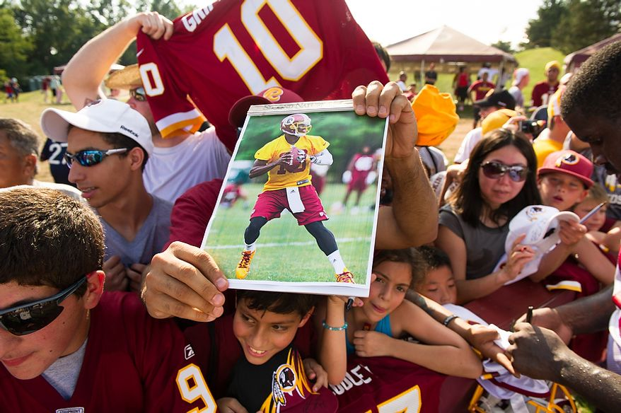 Fans scream and call for Washington Redskins quarterback Robert Griffin III (10) following afternoon practice on the first day of training camp at Redskins Park, Ashburn, Va., Thursday, July 26, 2012. (Andrew Harnik/The Washington Times)